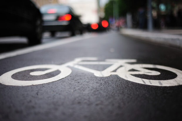 A close up image of a bike lane on a busy city street.
