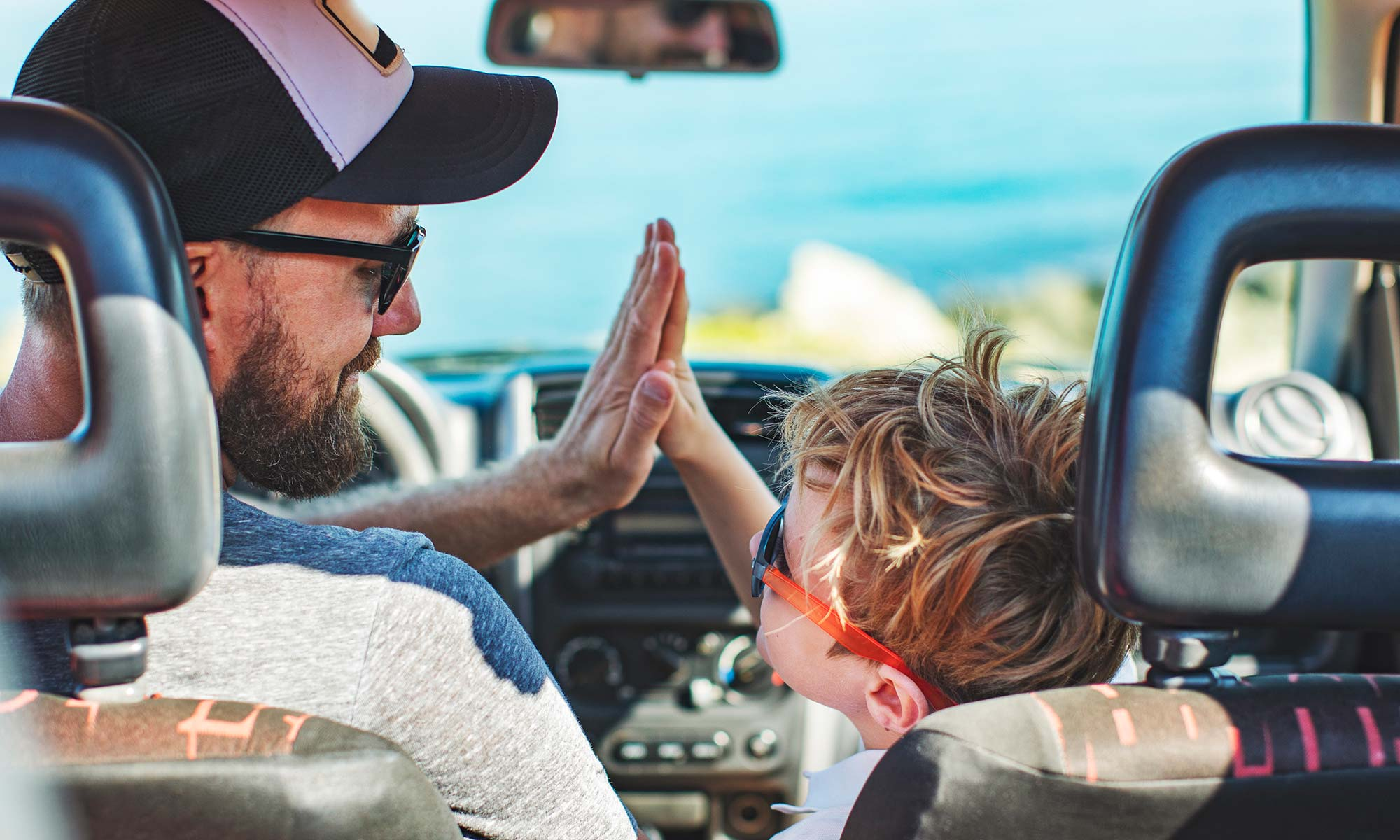A father and son high-fiving each other in their car.