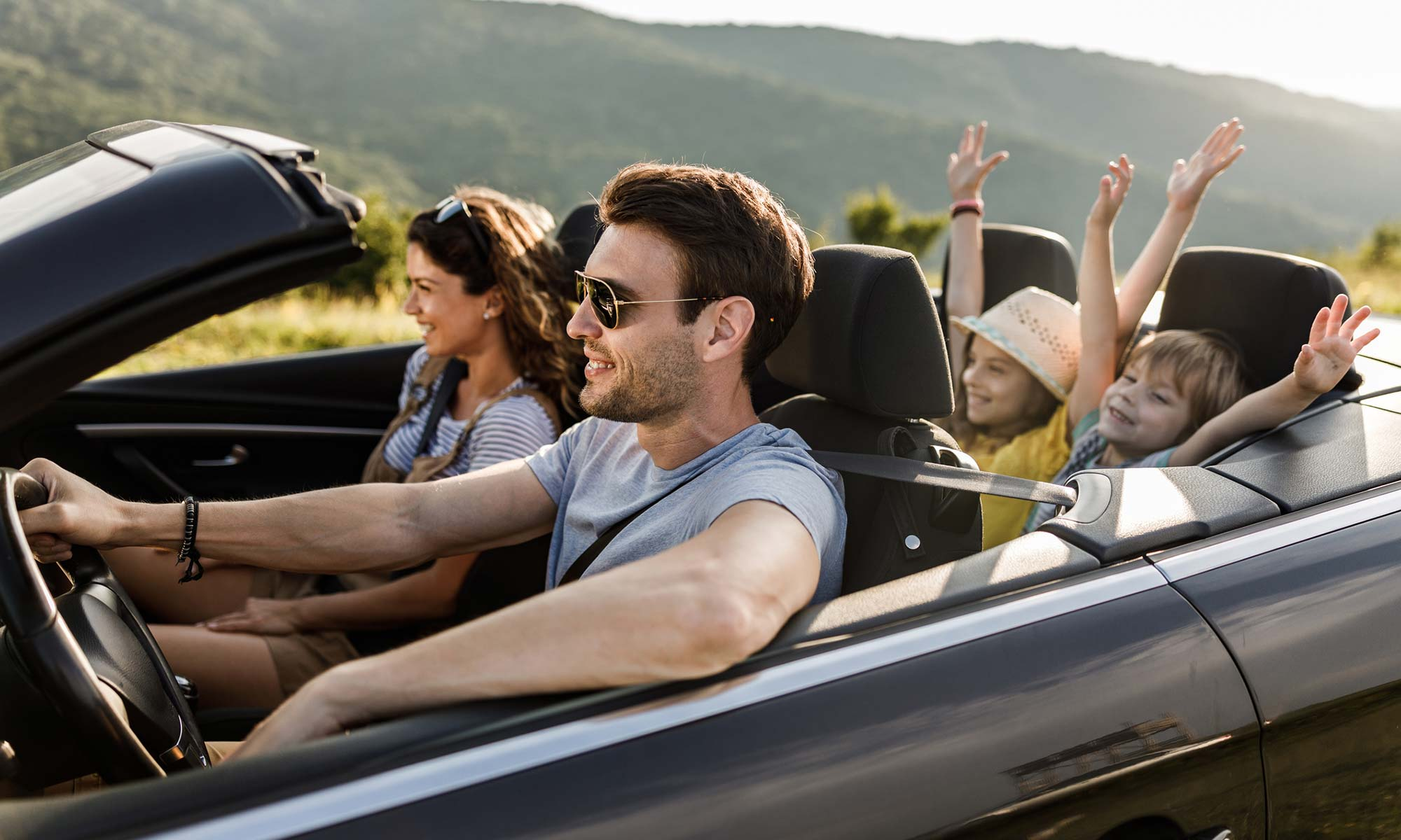 A family of four driving down the road in a convertible on a sunny day.