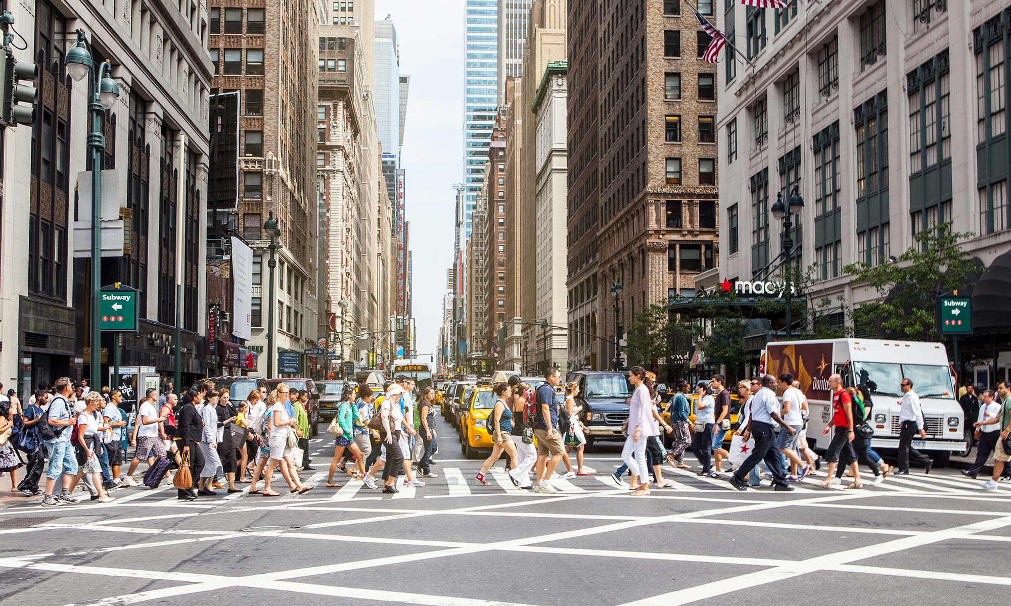 A large group of pedestrians crossing in front of a row of cars at a New York City crosswalk.