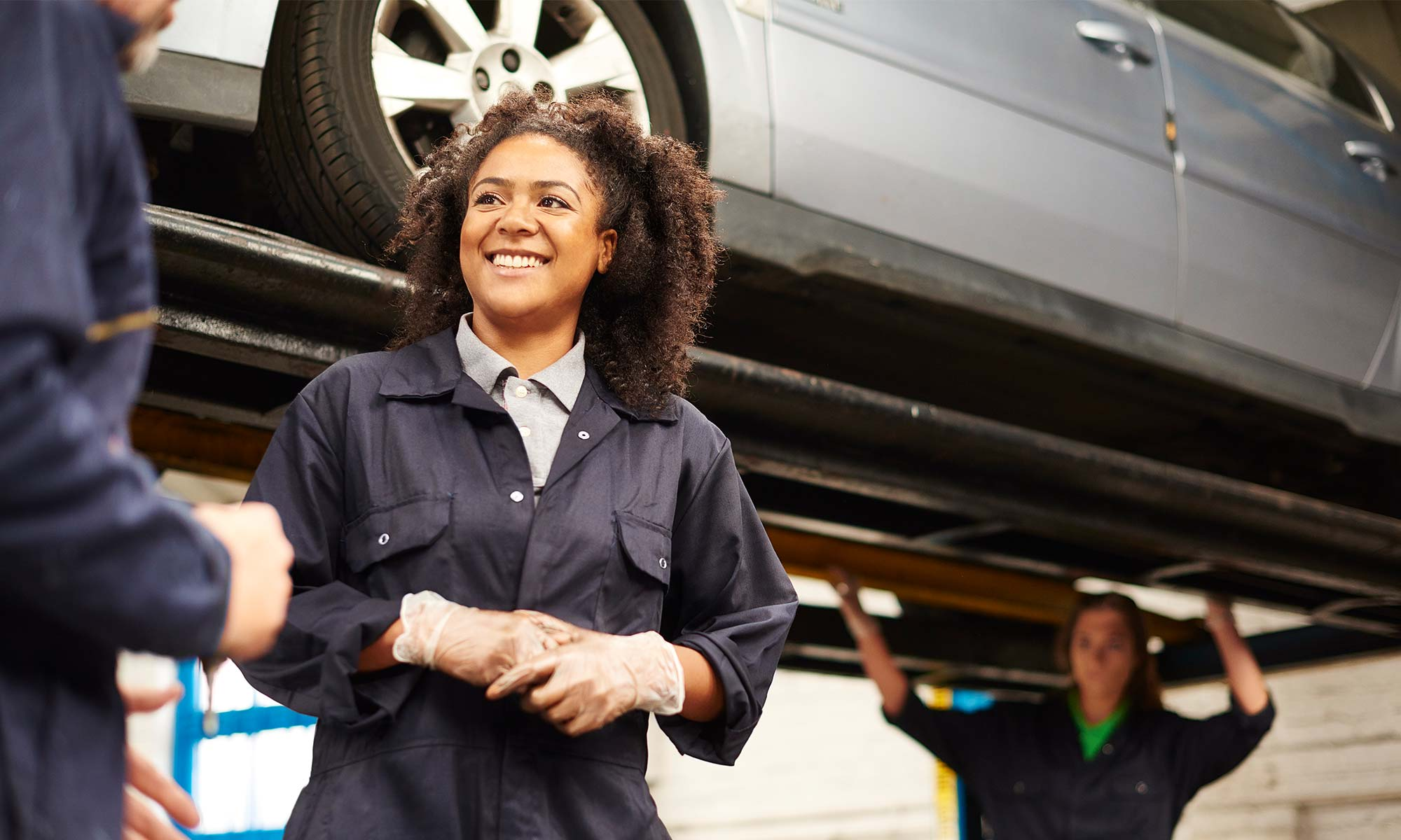 A female mechanic speaks with a customer while her colleague work on a vehicle behind her.s
