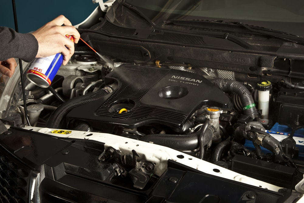 mechanic repairing car in shop using wd40 to reduce noise