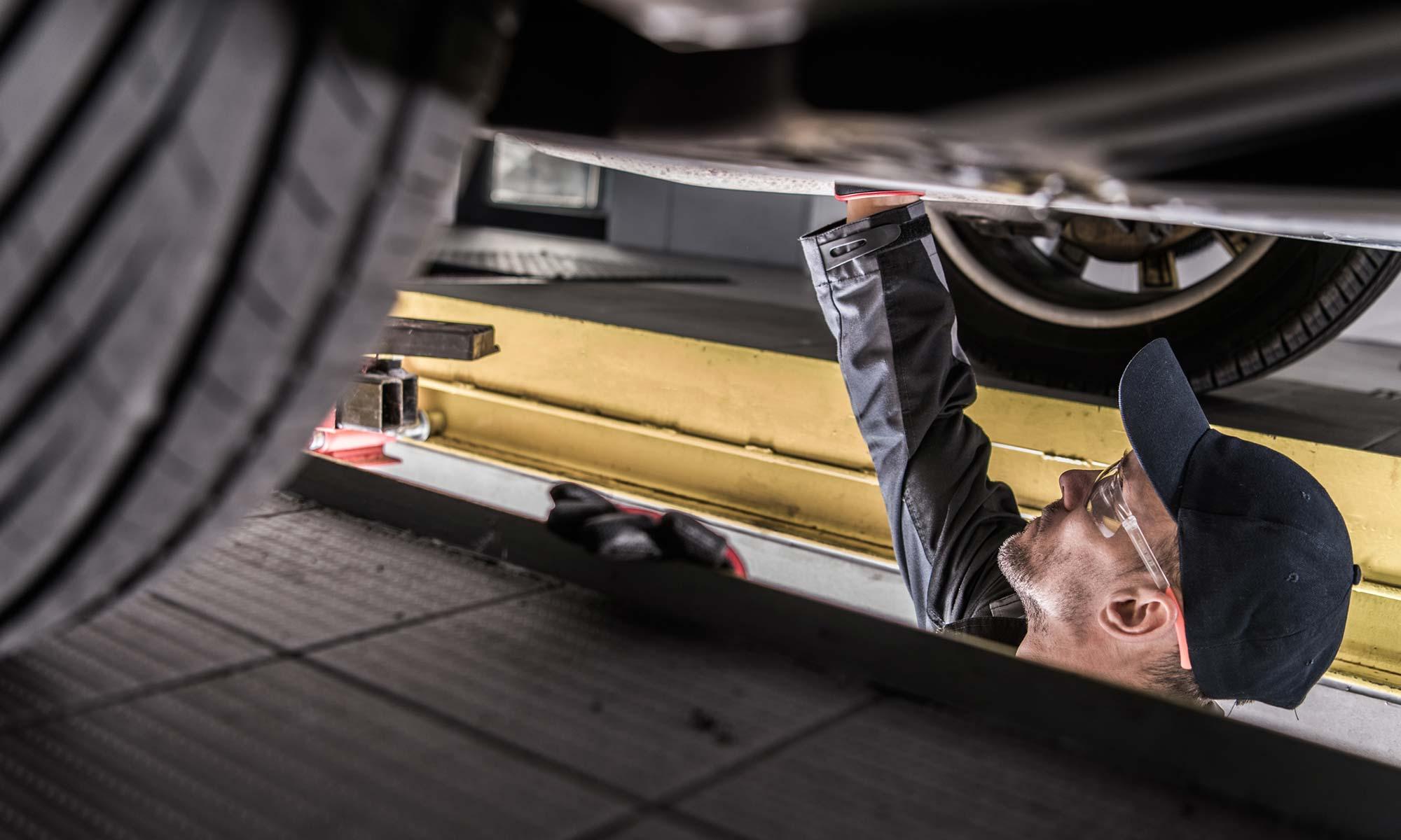 A male mechanic checks the drivetrain of a vehicle.