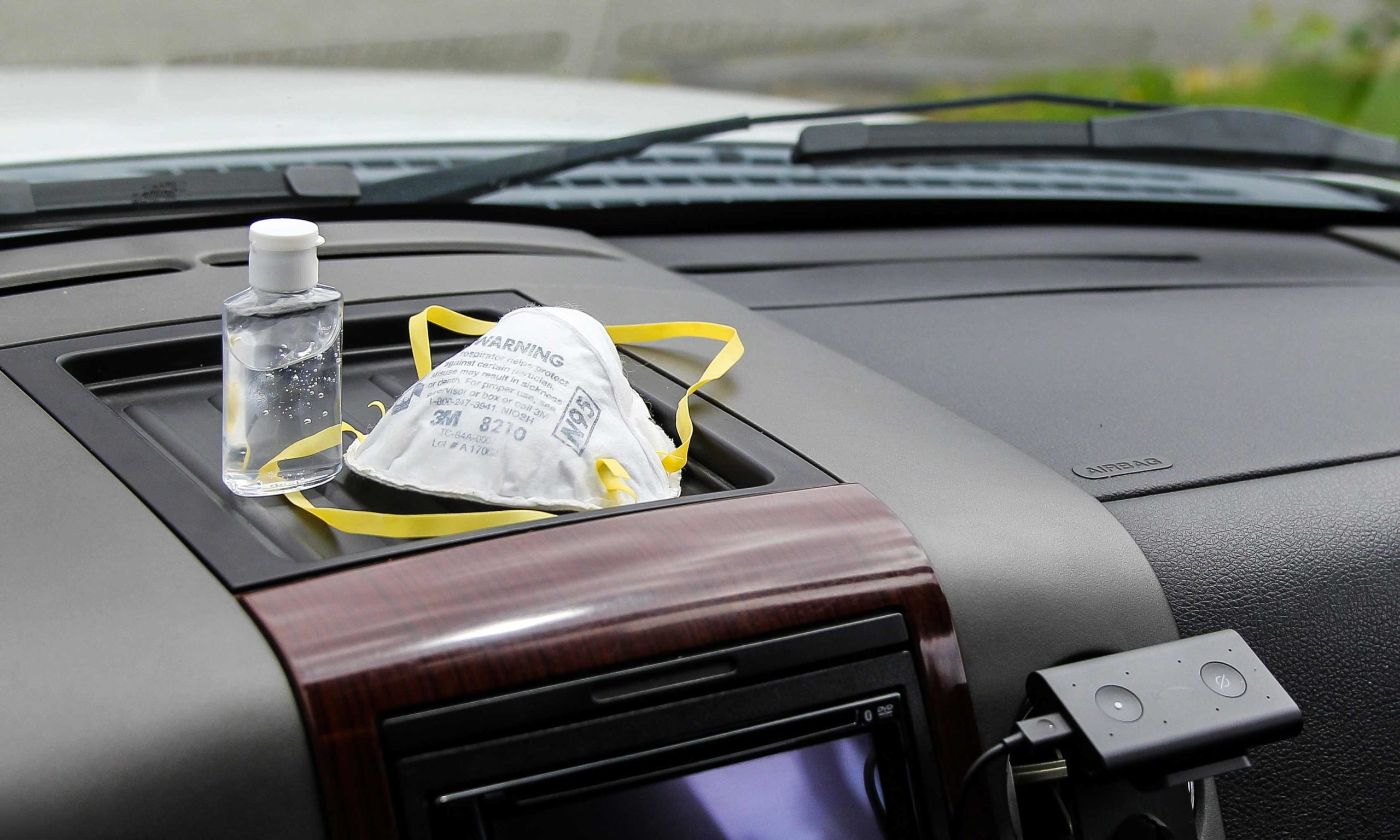 N95 mask and hand sanitizer on cars dashboard