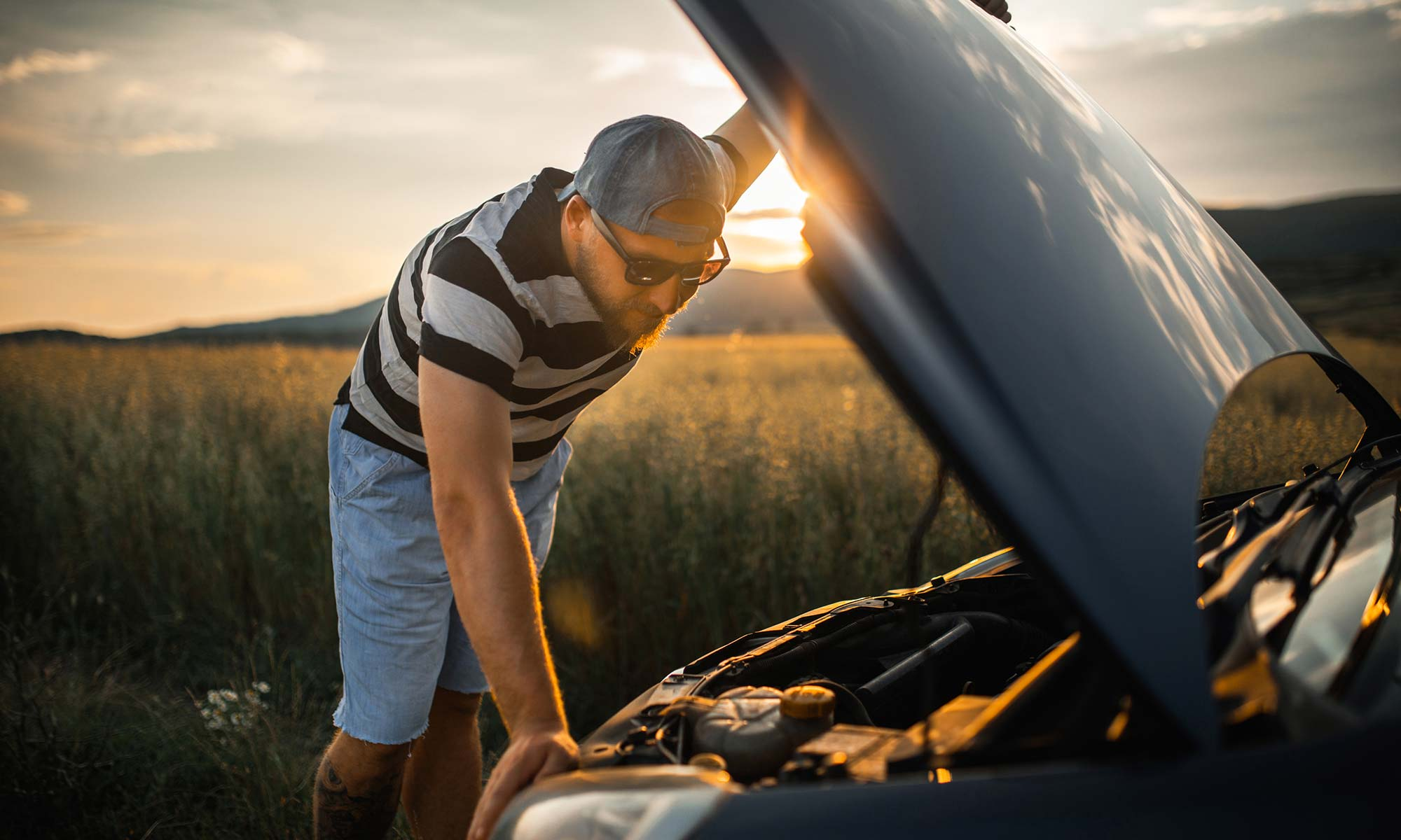 A young man in shorts and a t-shirt leans over the open hood of his car.