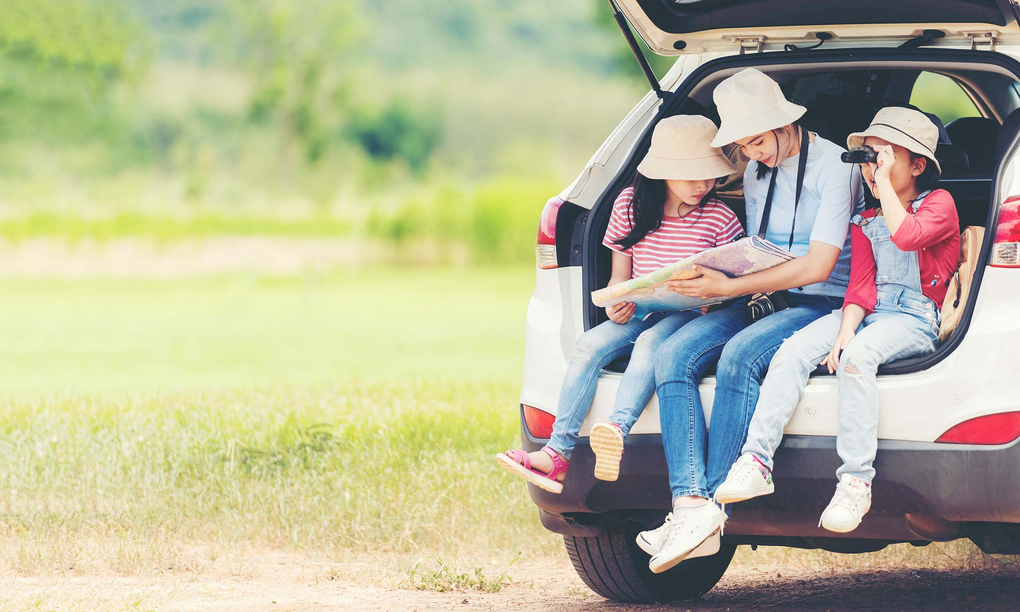 A mother and her two young daughters, all wearing hats, are sitting in the back of their open car trunk looking at a road trip map.