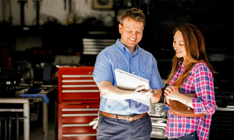 A male auto mechanic discusses a contract with a female customer.