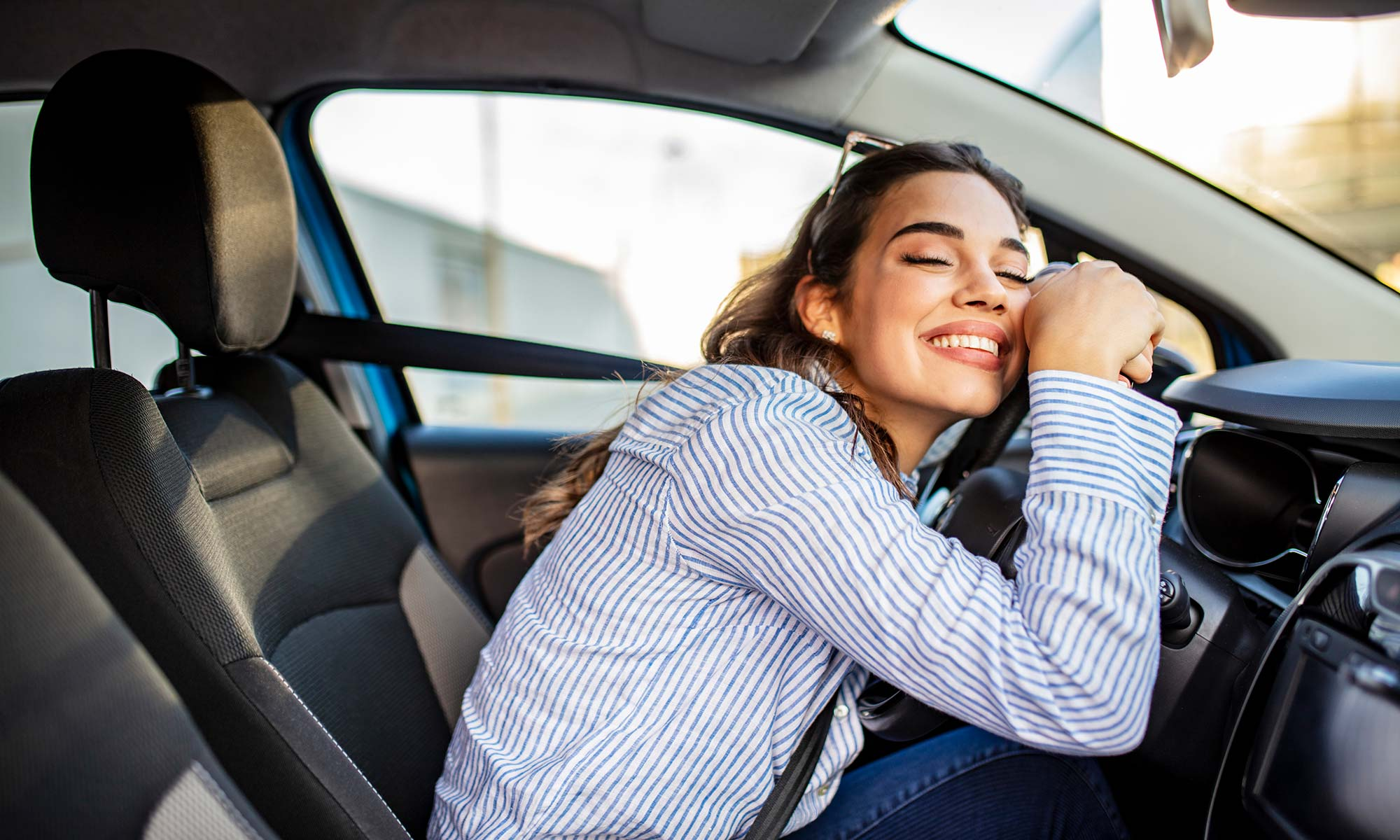 Image of happy woman leaning on her steering wheel