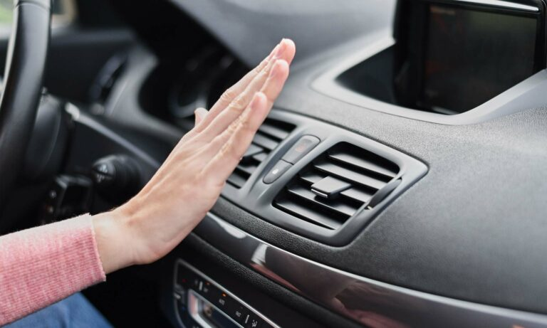 Women's hand held in front of her car's air conditioning vent to make sure it works.