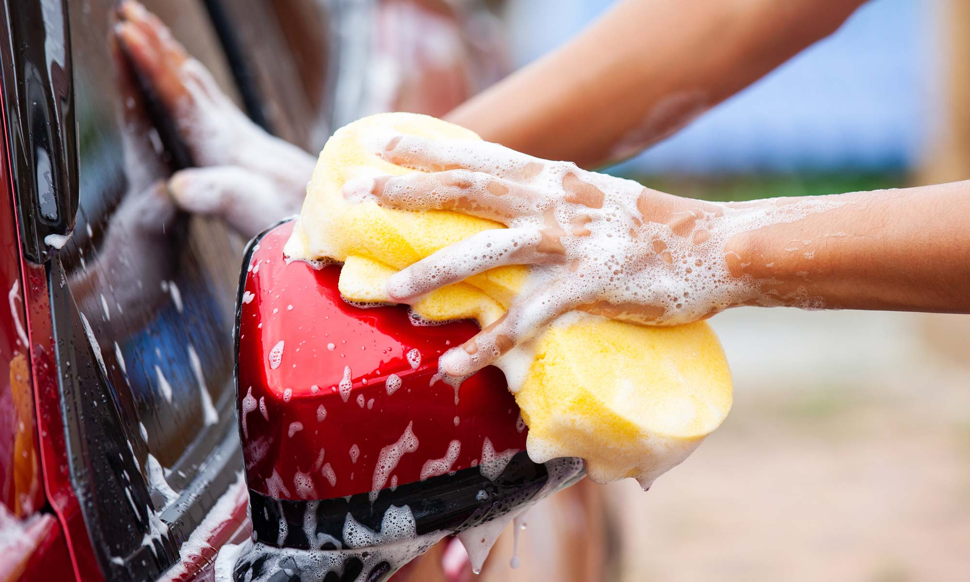 A close up image of a person washing a red car's driver-side mirror with sponge.