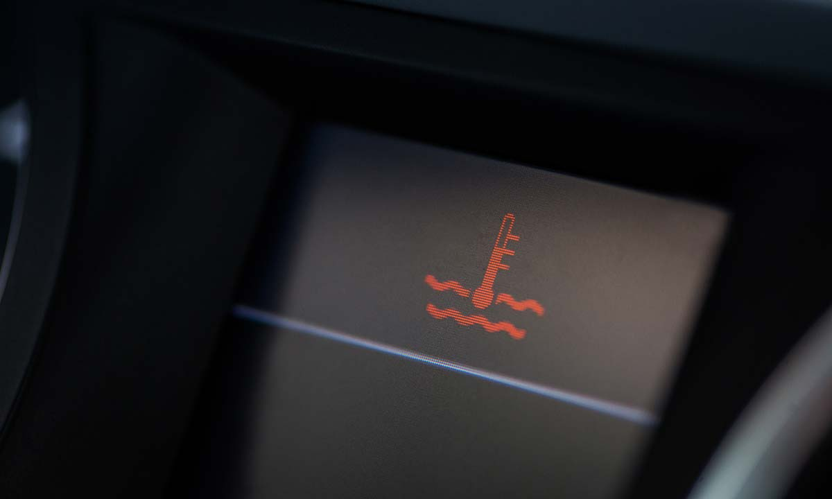 An image of the red thermometer warning indicator on a vehicle dashboard display, indicating possible engine overheating.