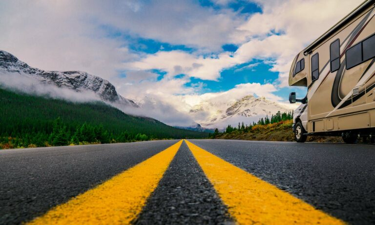 An RV drives down an open road with a scenic mountain view in the background.