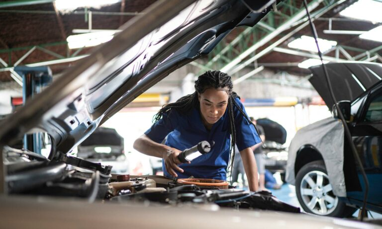 An African American female mechanic inspects the engine of a car.