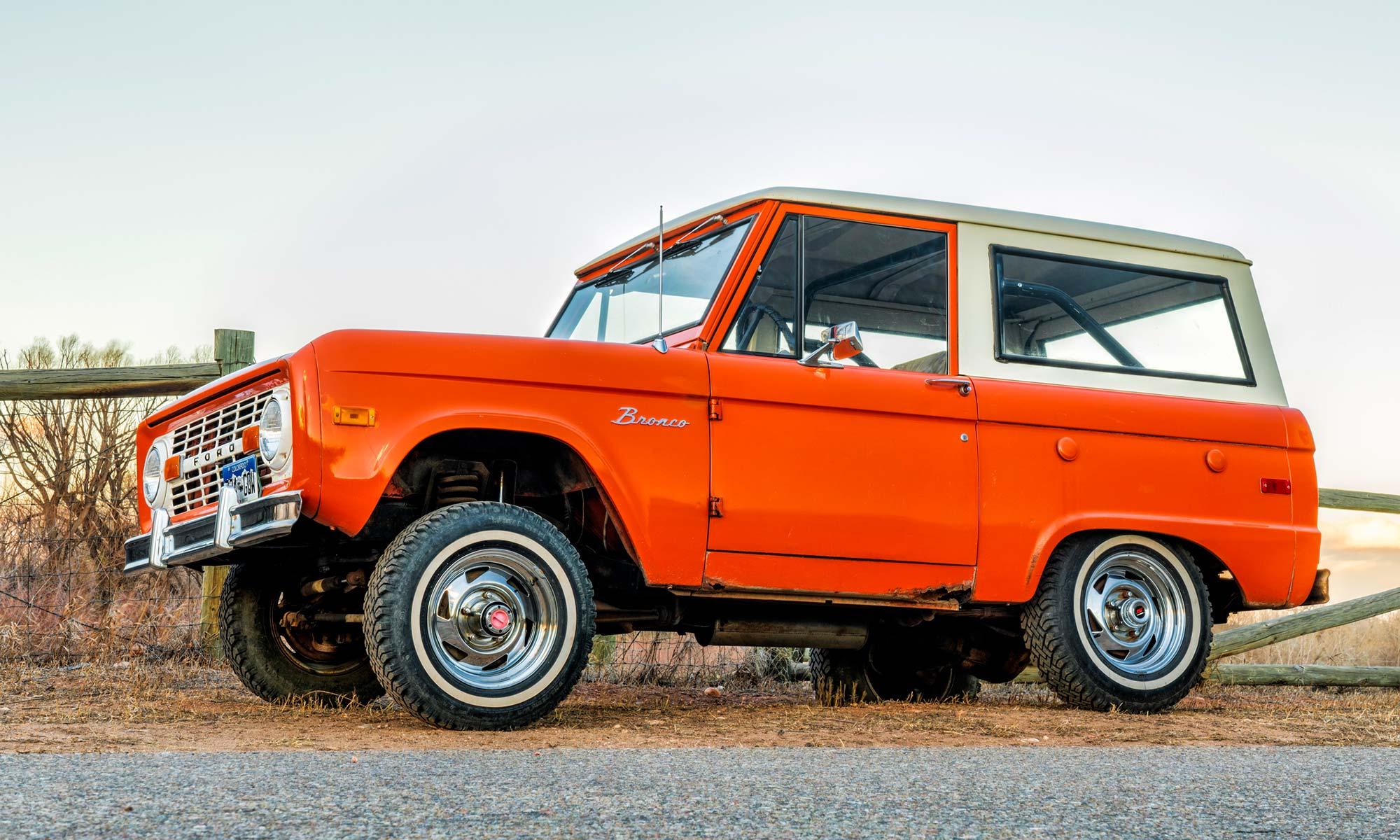 A vintage, first generation, orange Ford Bronco ranger wagon parked on a rural road.
