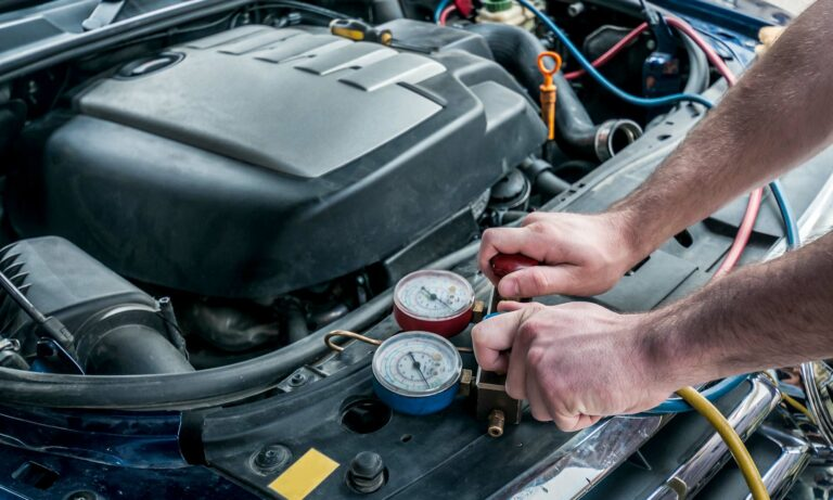 A male car mechanic's hands placing two Freon charging cables to a car's engine.