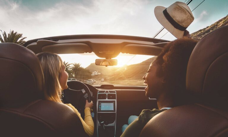 Two female friends having fun and laughing while driving a convertible during sunset with the top down.