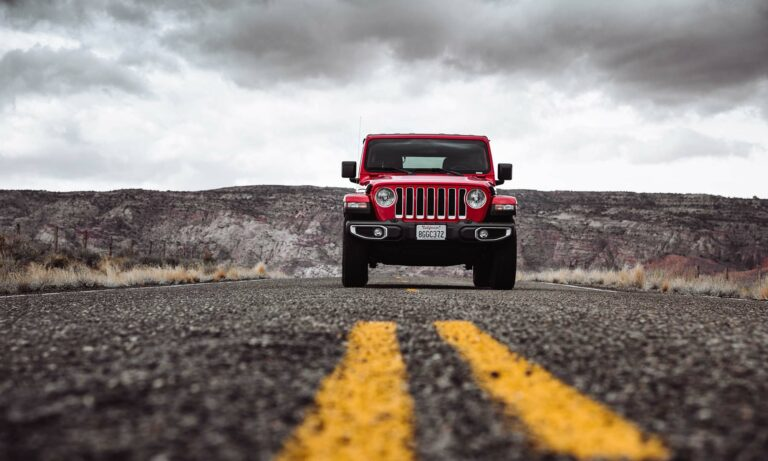 A red Jeep Wrangler driving down a desert road.