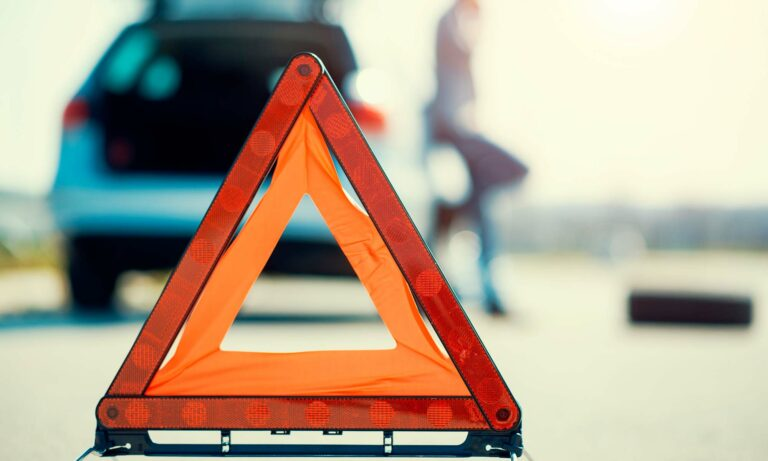 A close up of an orange warning triangle placed on the road in front of a stalled vehicle.