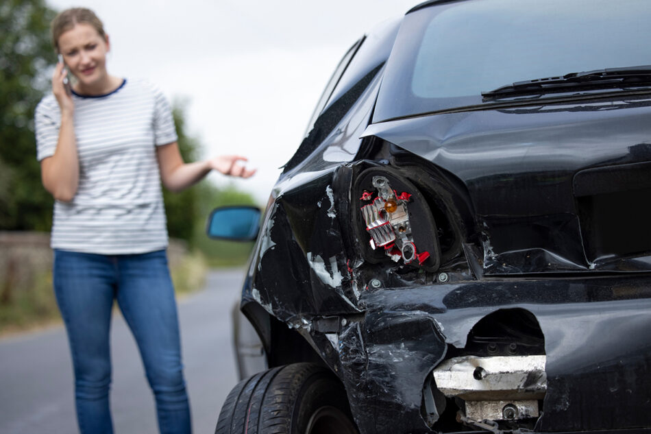 A woman standing in front of her damaged car talking on the phone.