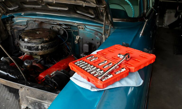 An open toolbox sits next to a car engine.
