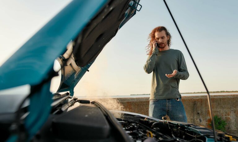 A man talking on the phone as he standing next to his open car hood with the engine smoking.