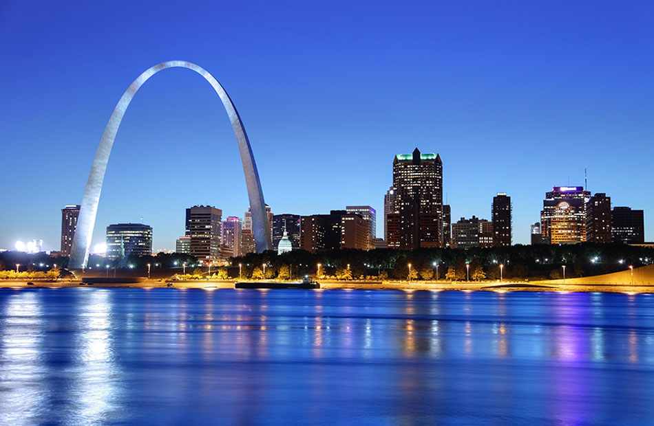 An image of the Gate Arch and St. Louis skyline illuminated at night.
