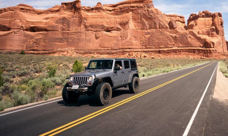 A grey Jeep Wrangler driving down a desert road.