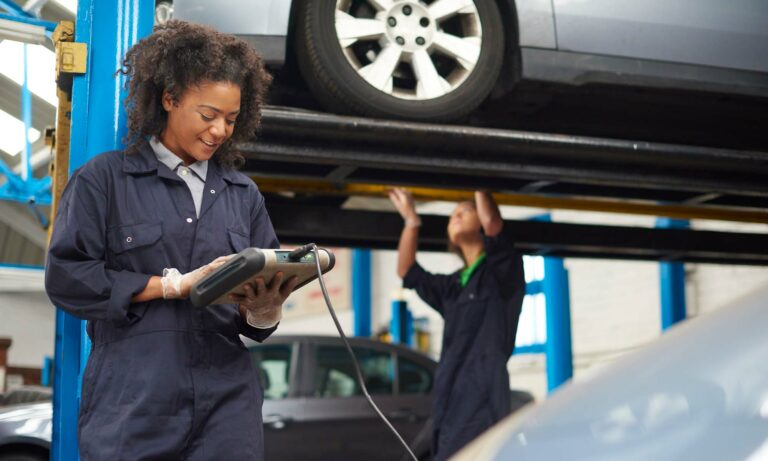 A female mechanic checks a reading on a sensor attached to a vehicle in her shop.