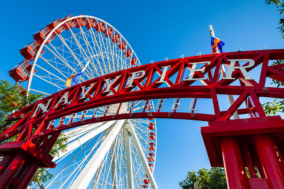 The sign for Navy Pier in Chicago in front of a Ferris wheel.