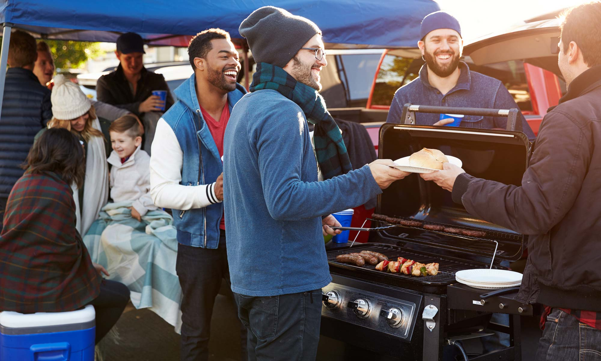 A group of people enjoying a tailgate party in the Fall.