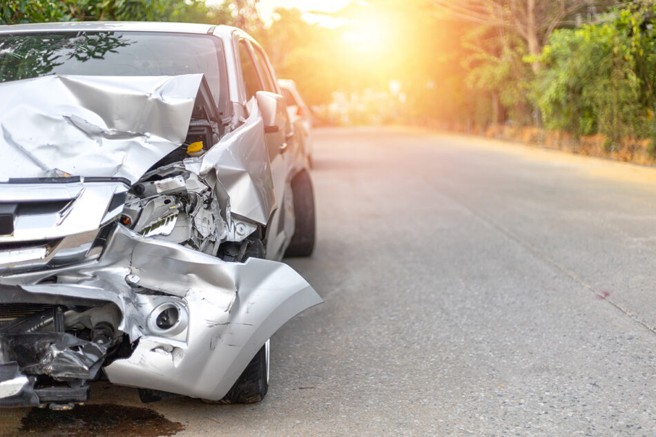 A heavily damaged silver car on the side of the road.