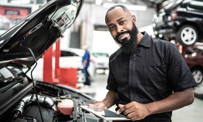 A mechanic in front of a car.
