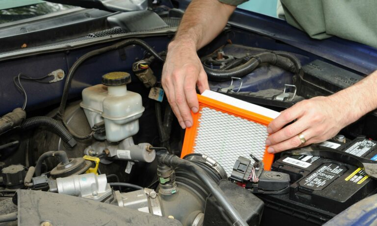 A mechanic changing a car's engine air filter.