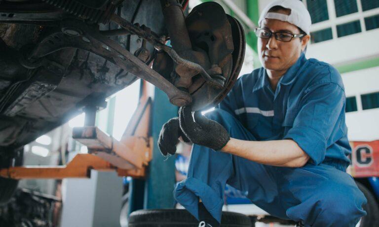 A vehicle mechanic working on a car.