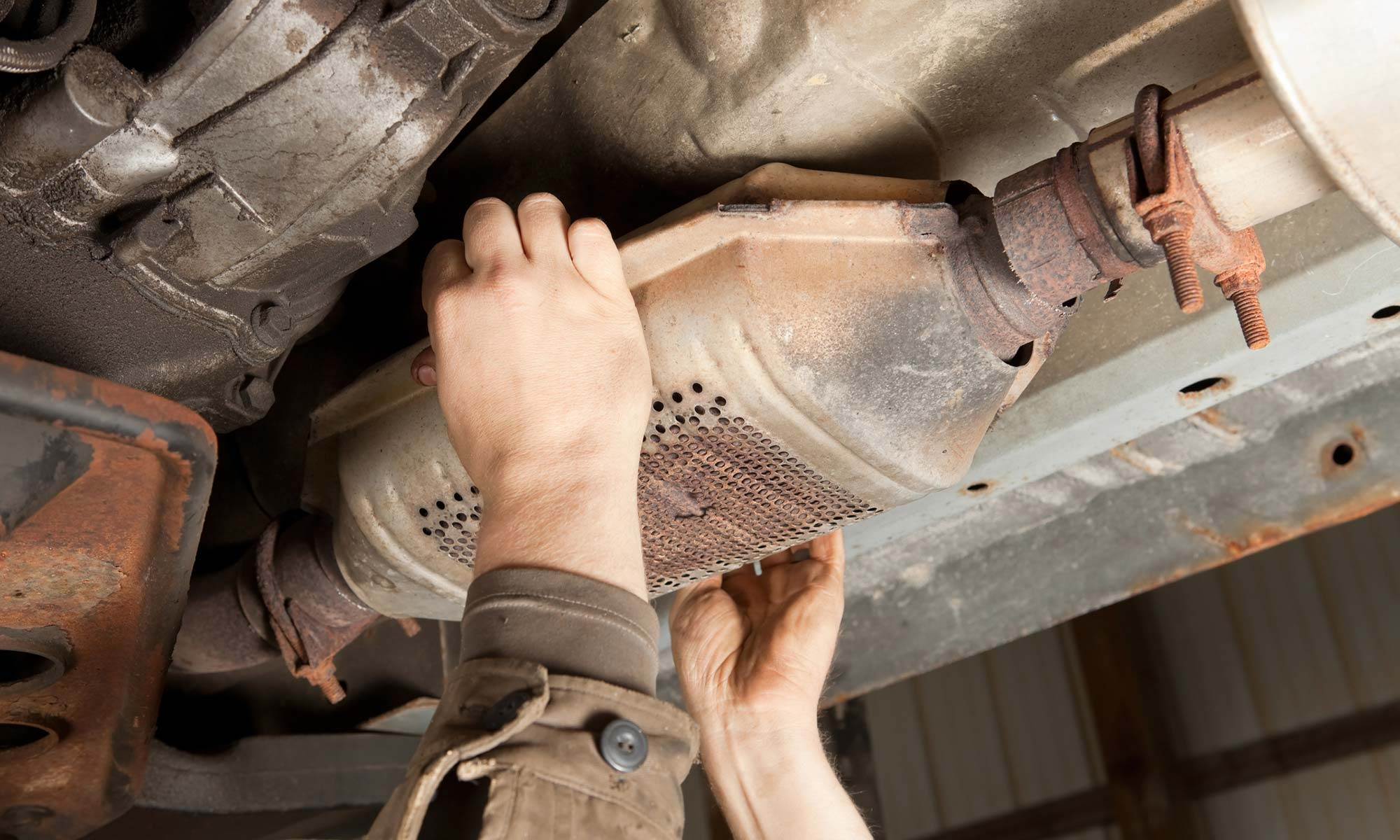 A mechanic fixing a catalytic converter.