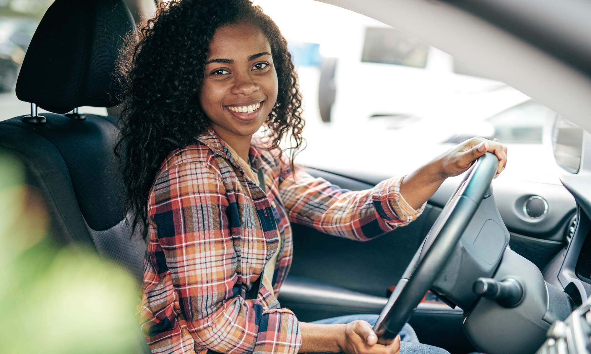 A young woman smiles while in the driver seat of her car.