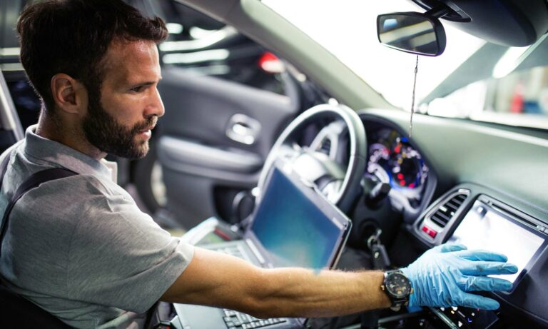 A mechanic using a laptop to diagnose an issue with a vehicle.
