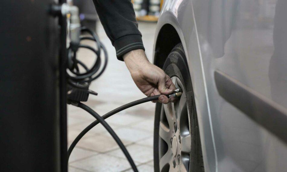 A man fills his car tire with air at an air pump.
