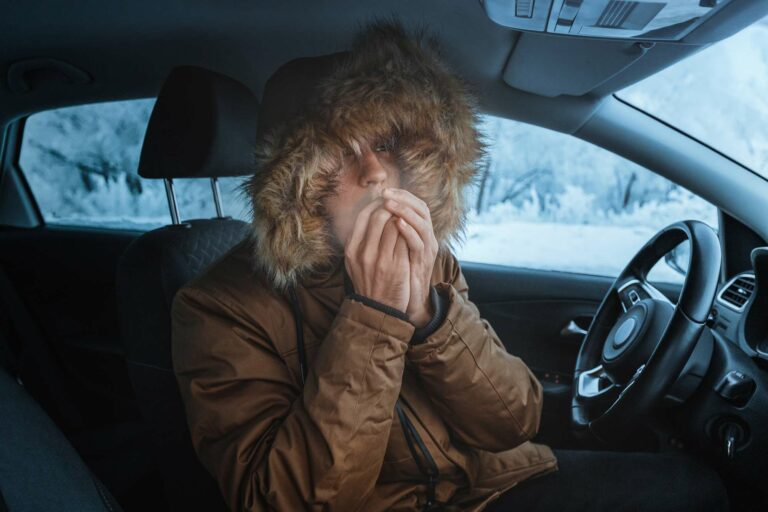A young man sitting in his car with a broken heater.