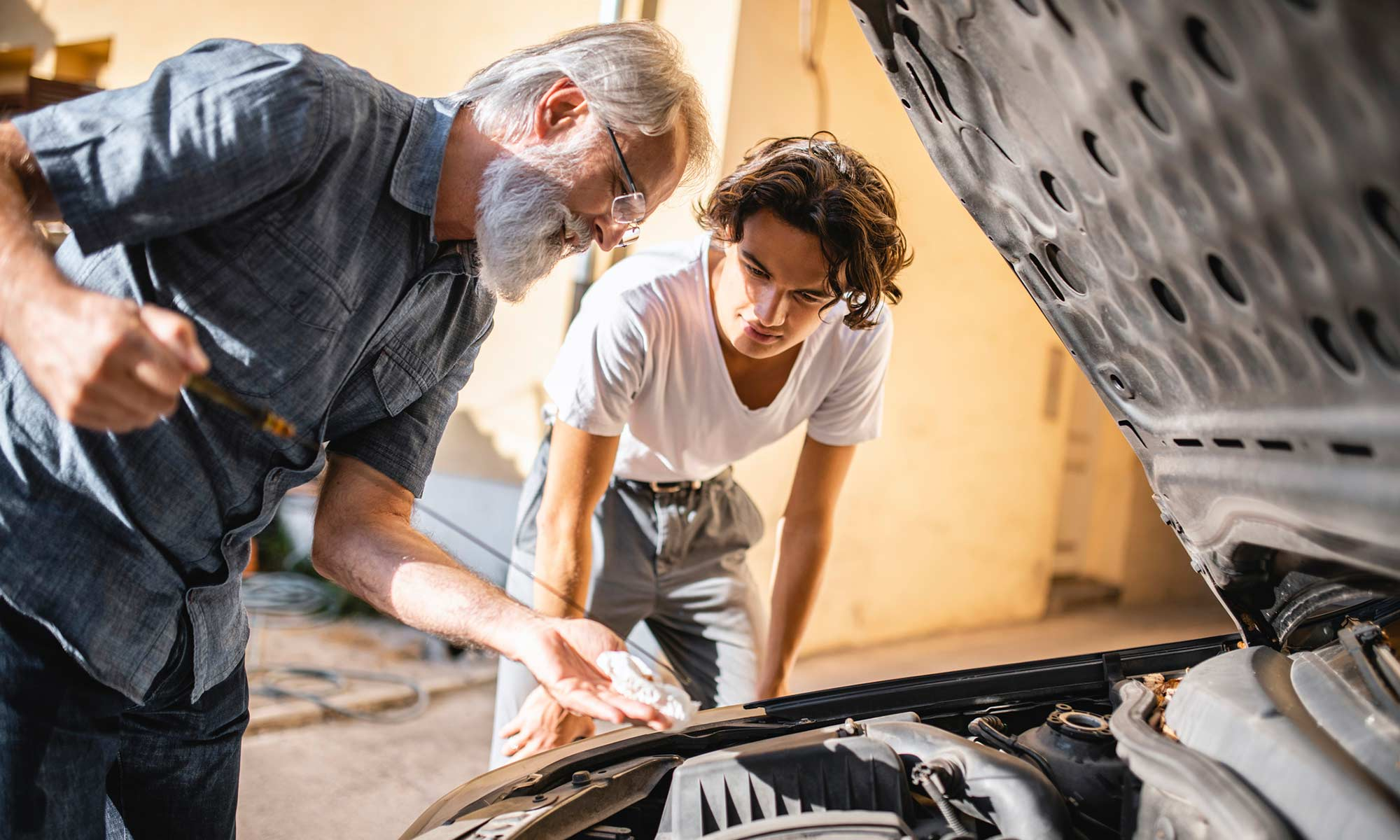 A grandfather and grandson working on a vehicle at home.