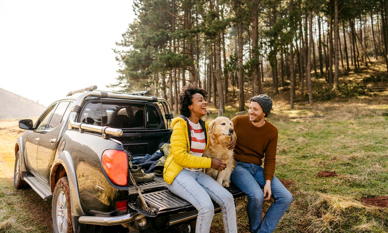 A couple and their dog outside their vehicle.