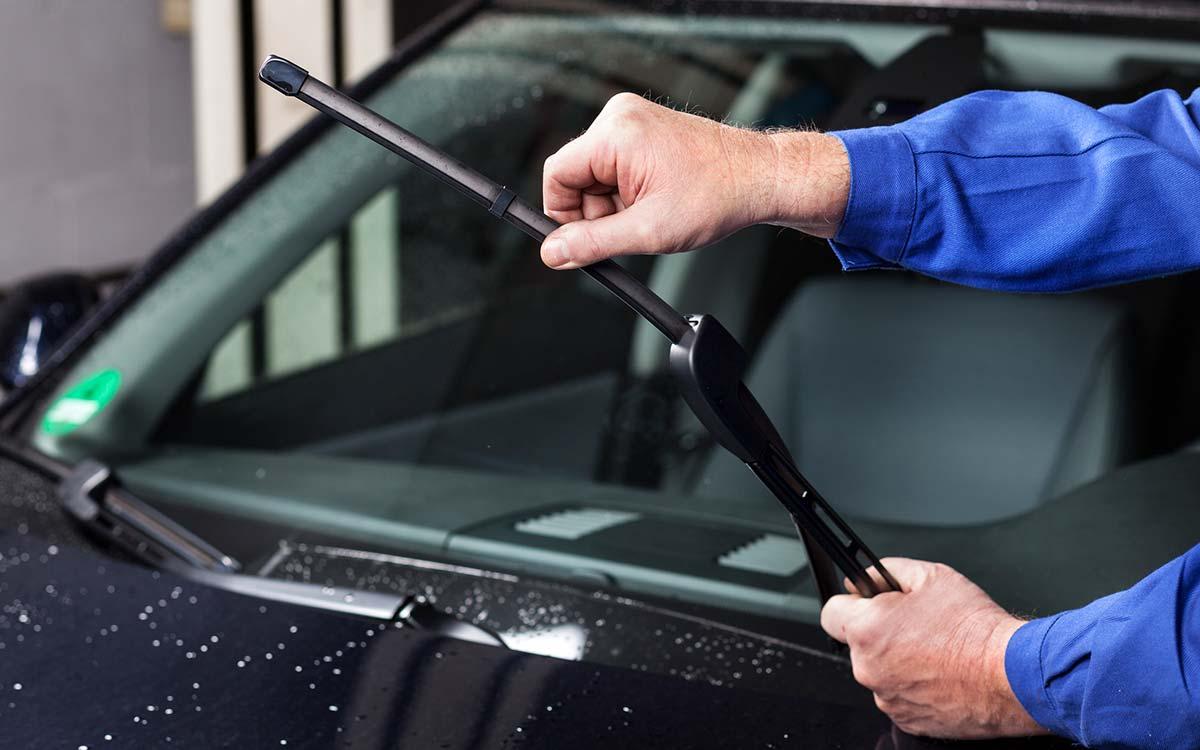 A man changing a car wiper blade.