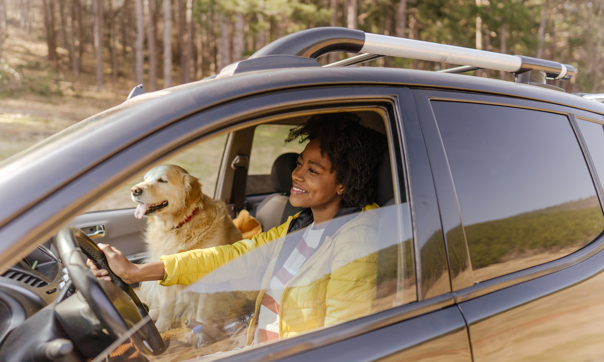 Photo of a young smiling woman driving a car. Her dog is sitting on a passenger seat